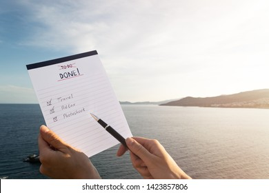 """Female hands holding a notepad with """"Done"""" list with handwritten text """"Travel"""", """"Relax"""", """"Photoshoot"""". Checkboxes, copy space, pen."""