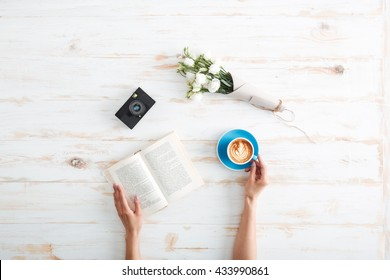 Female hands holding open book and coffee cup on the wooden desk