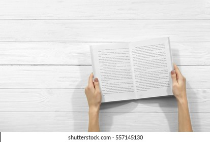 Female hands holding opened book on wooden background