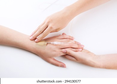 Female hands holding patient hand with dropper needle on bed close-up