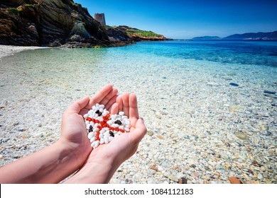 Female hands holding pebbles forming a heart shape depicting Four Moors flag of Sardinia island, with typical south Sardinia beach in background. The flag of Sardinia - la bandiera sarda