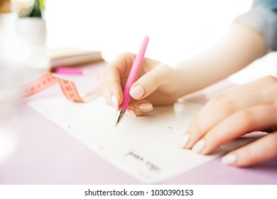 Female hands holding pen, writing. Side view on woman on trendy color pink desk. Woman and stilish workplace. Women's Day concept