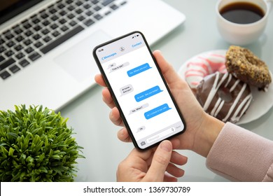 female hands holding phone with app messenger on the screen above the table in office