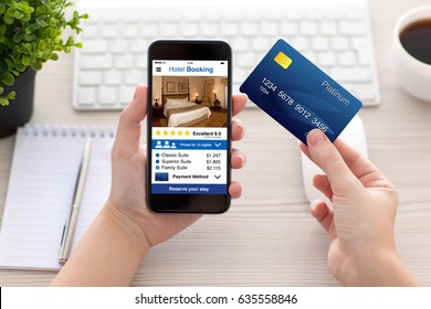 female hands holding phone with app hotel booking screen and credit card in office