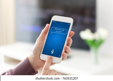 Female hands holding phone with app personal assistant on screen in room home