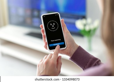 Female hands holding phone with face ID scanning on the screen in room home