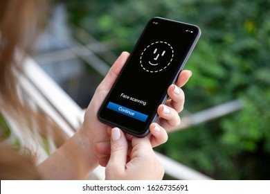 female hands holding phone with face ID scanning on the screen background of nature