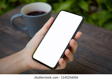 female hands holding phone with isolated screen over the table