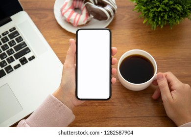 female hands holding phone with isolated screen above the table in the office