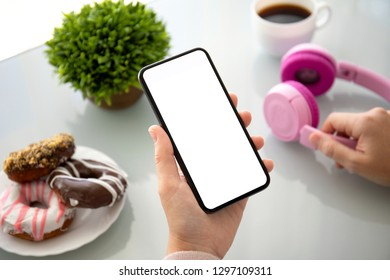 female hands holding phone with isolated screen above the table with headphones