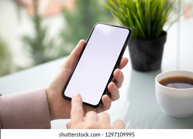female hands holding phone with isolated screen in a summer cafe