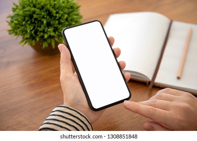 female hands holding phone with isolated screen above the table in office