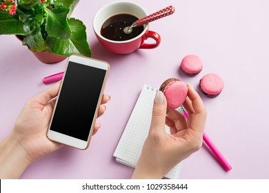 Female hands holding phone. Top view on french macarons on trendy color pink desk. Woman and stilish workplace. Cup of coffee, phone, notebook. Breakfast, cakes, coffee. Women's Day concept