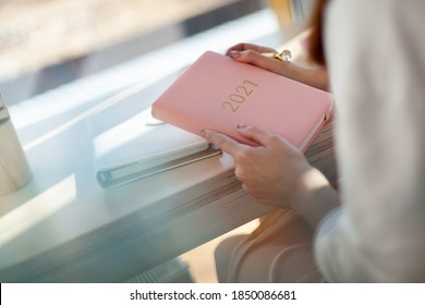 Female hands holding pink or coral coloured leather diary 2021 and pen while sitting near a window Concept of planning personal future goals and ideas for new year 2021. Copy space.