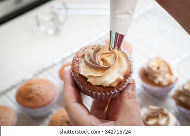 female hands holding piping bag filled with cream cheese and coffee frosting decorating cupcakes