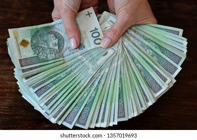 Female hands holding a lot of Polish 100 zlotys