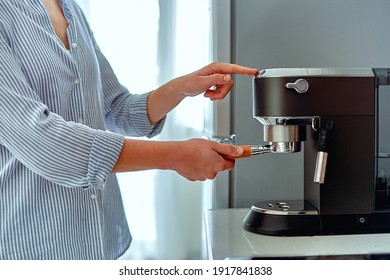 Female hands holding portafilter and making fresh aromatic coffee at home using a modern coffee maker