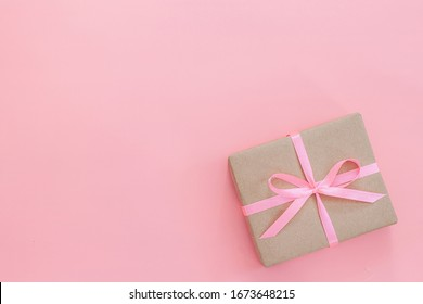 Female hands holding present box or gift box package in craft paper over white background. Top view, flat lay