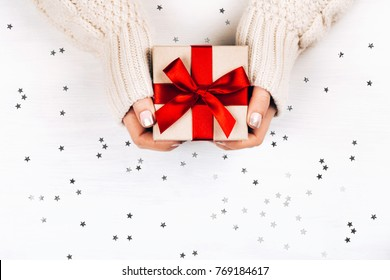 Female hands holding present with red bow on white rustic background with silver sparkles. Festive backdrop for holidays: Birthday, Valentines day, Christmas, New Year. Flat lay style