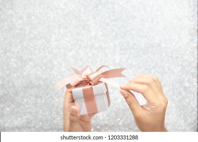 Female hands holding or pulling ribbons of a small gift box with copy space for text and silver glitter background.