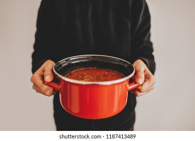 Female hands holding red pot with vegetable soup. Healthy food concept