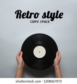 Female hands holding a retro vinyl record on a gray background. Top view, minimalism.