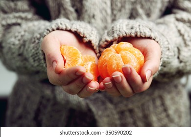 Female hands holding ripe mandarins, close up