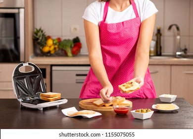 Female hands holding a sandwich and adding ketchup on it with a spoon; woman making hot sandwiches in a sandwich maker for breakfast