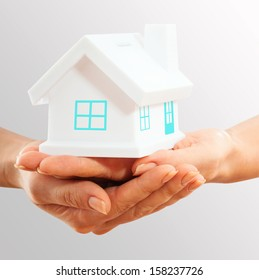Female hands holding saving small house with roof