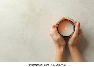 Female hands holding scented candle, top view