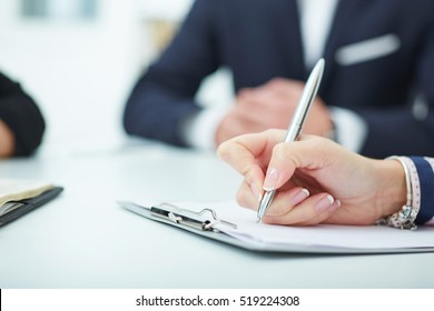 Female hands holding a silver pen closeup.  Business job offer, financial success, certified public accountant concept.