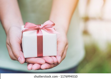 Female hands holding a small gift wrapped with pink ribbon. Selective focus,Selective focus,Valentines day