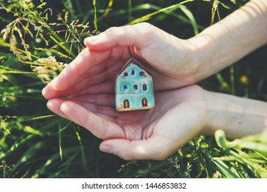 female hands holding small house, real estate, home protection and safety concept, natural background
