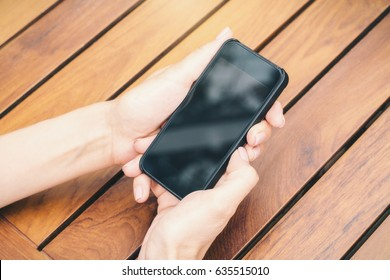 Female hands holding smartphone with blank screen above wooden plank desktop. Mock up
