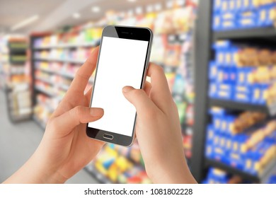 Female hands holding smartphone with empty screen, blurred grocery store in background. Online shopping concept, Mockup