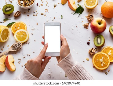 Female hands holding smartphone on healthy food background, woman using phone search mobile apps with diet nutrition plan cooking, vegan fruit granola seeds on white table, top view, mock up screen