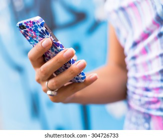 Female Hands holding smartphone. Young tanned  woman holding mobile phone,checking news and typing sms, wearing blue dress and ring.Mobile in bright cover.