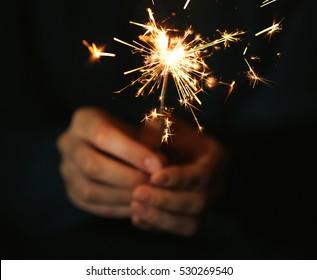 Female hands holding sparkler on dark background, close up
