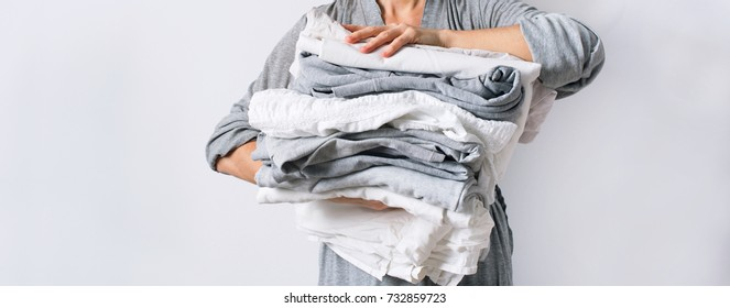 female hands holding stack monochrome gradient white gray black bed linen textiles clothing background pile concept