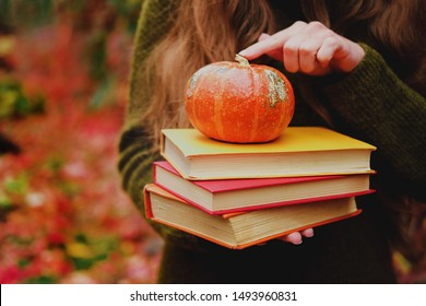 Female hands holding a stack of three vintage paper books and small pumpkin among colorful ivy in autumn