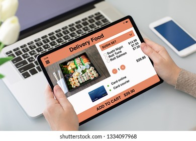 female hands holding tablet with app delivery food on the screen above laptop and phone
