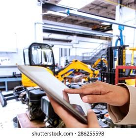 Female hands holding tablet pc against mechanic workshop