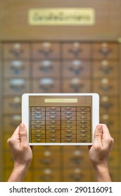Female hands holding tablet taking pictures of library catalog cards with thai character