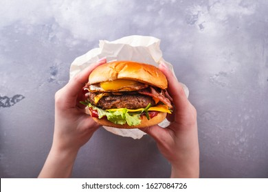 Female hands holding tasty beef burger with fried egg. Top view. Fastfood. Lifestyle