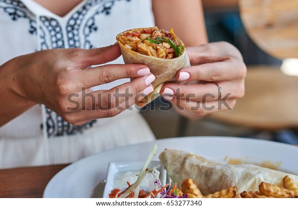 Female hands holding tasty mexican burrito with different ingredients inside. Woman eating delicious pita and salad with French fried potato.