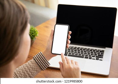 female hands holding touch phone with isolated screen above the table with laptop in the office