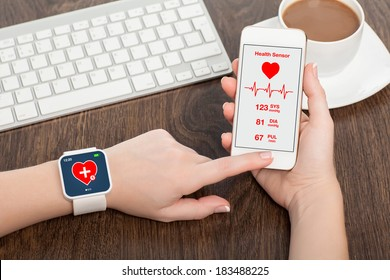 Female hands holding touch phone and smart watch with mobile app health sensor