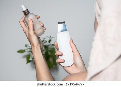 Female hands holding ultrasonic skin scrubber and beauty serum. Skincare electrical gadget for procedure at home.