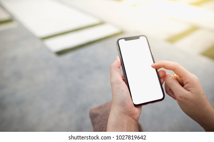 Female hands holding and using a mobile phone with a white screen display