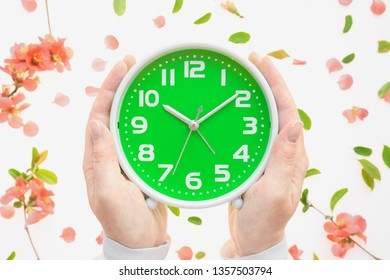 Female hands holding vintage alarm clock flat lay with colorful springtime floral decoration of petals and leaves